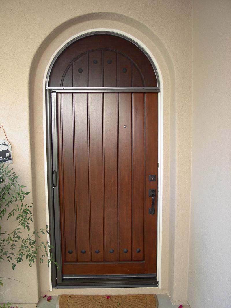 arch Retractable Screen Doors with black handle matched with cream wall