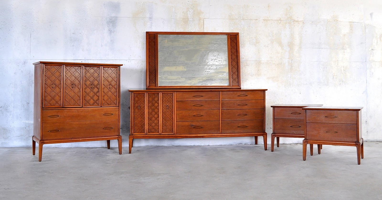awesom triple mid century design with a big mirror and some carving motif