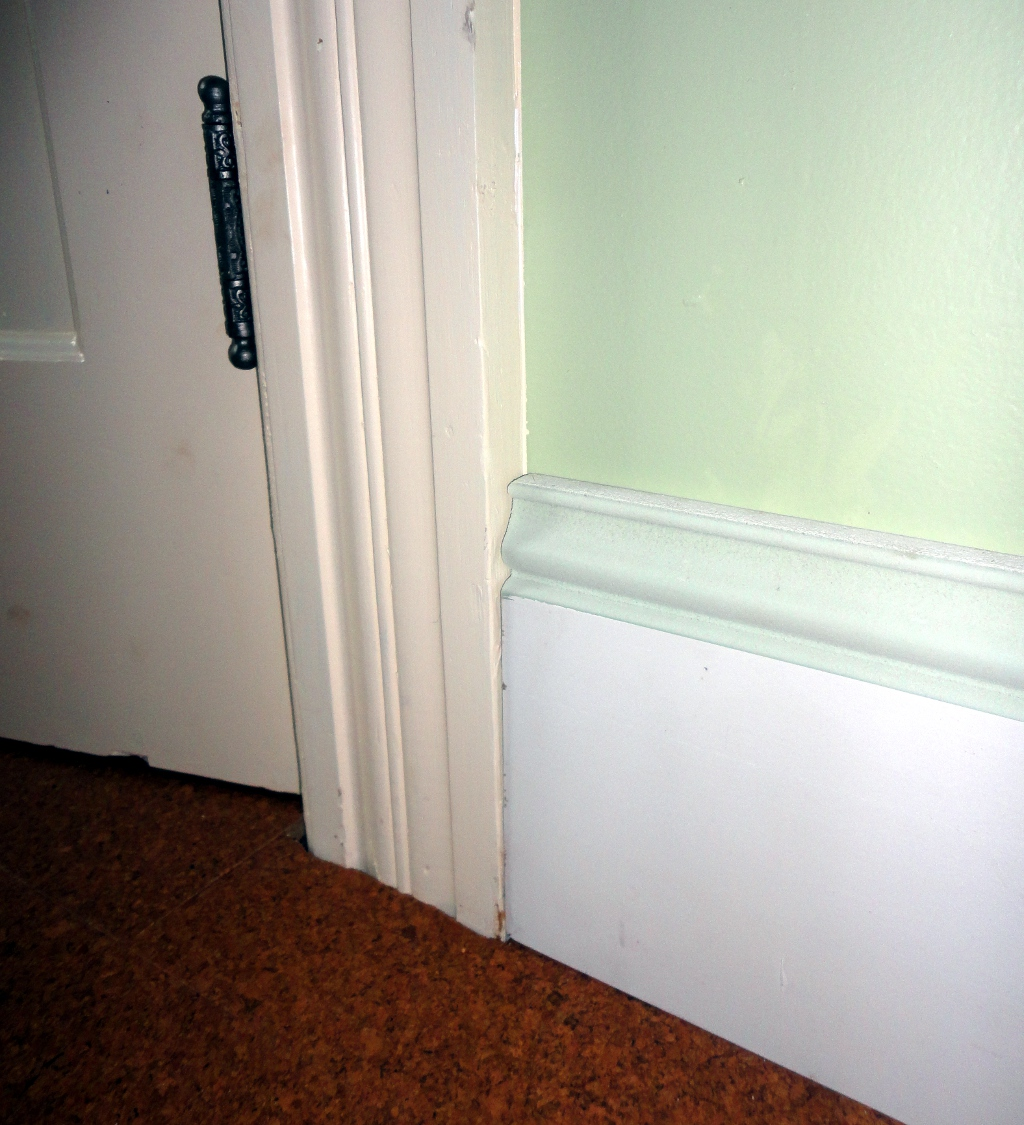 baseboard molding with green wall and white door