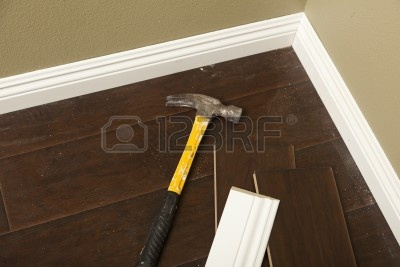 Baseboard Molding With Olive Wall And Laminate Flooring Plus Hammer