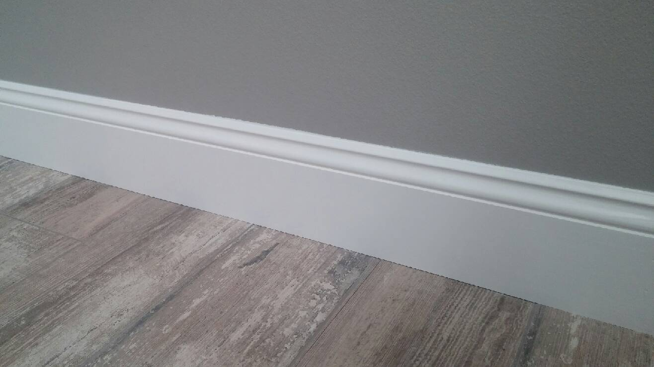 baseboard molding with wood floor and grey wall