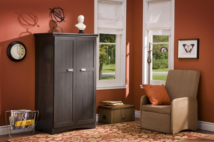 Black Computer Armoire With Orange Wall And Single Sofa And Floral Carpet For Family Room Decor