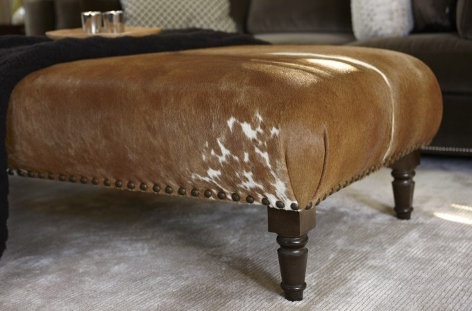 Brown Cowhide Ottoman With Wooden Legs On Carpet