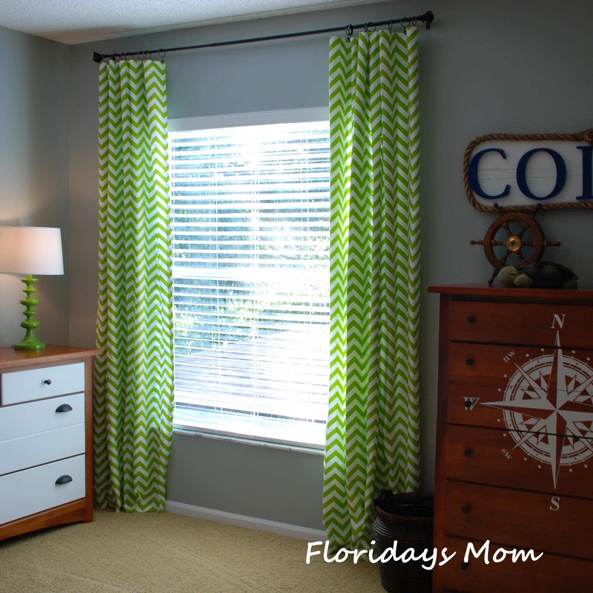chevron curtains in green with wheat wall and green table standing lamp