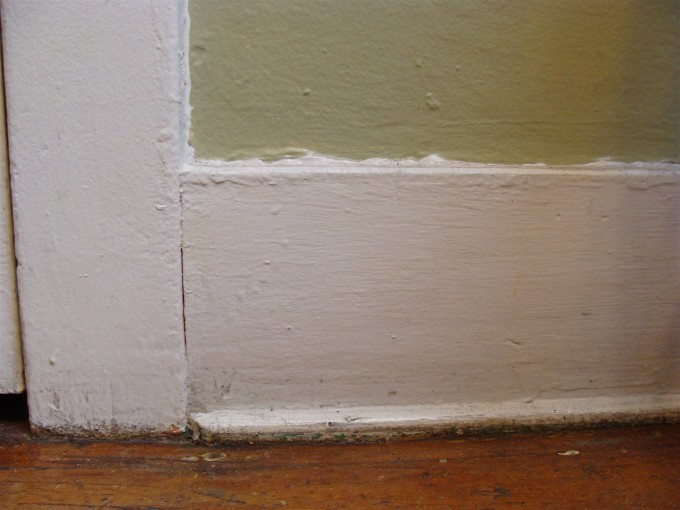 Craftsman Baseboard Molding With Green Wall And Wooden Floor