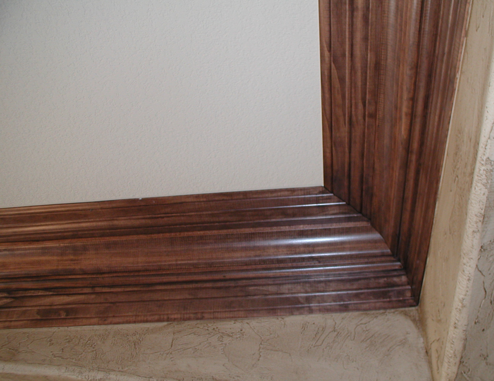 crown baseboard molding matched perfectly with white wall and cream ceramic floor