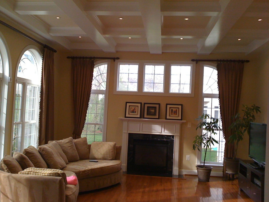 Custom Coffered Ceiling with lights matched with cream wall plus window and curtains and fireplace plus wooden floor for family deoration ideas