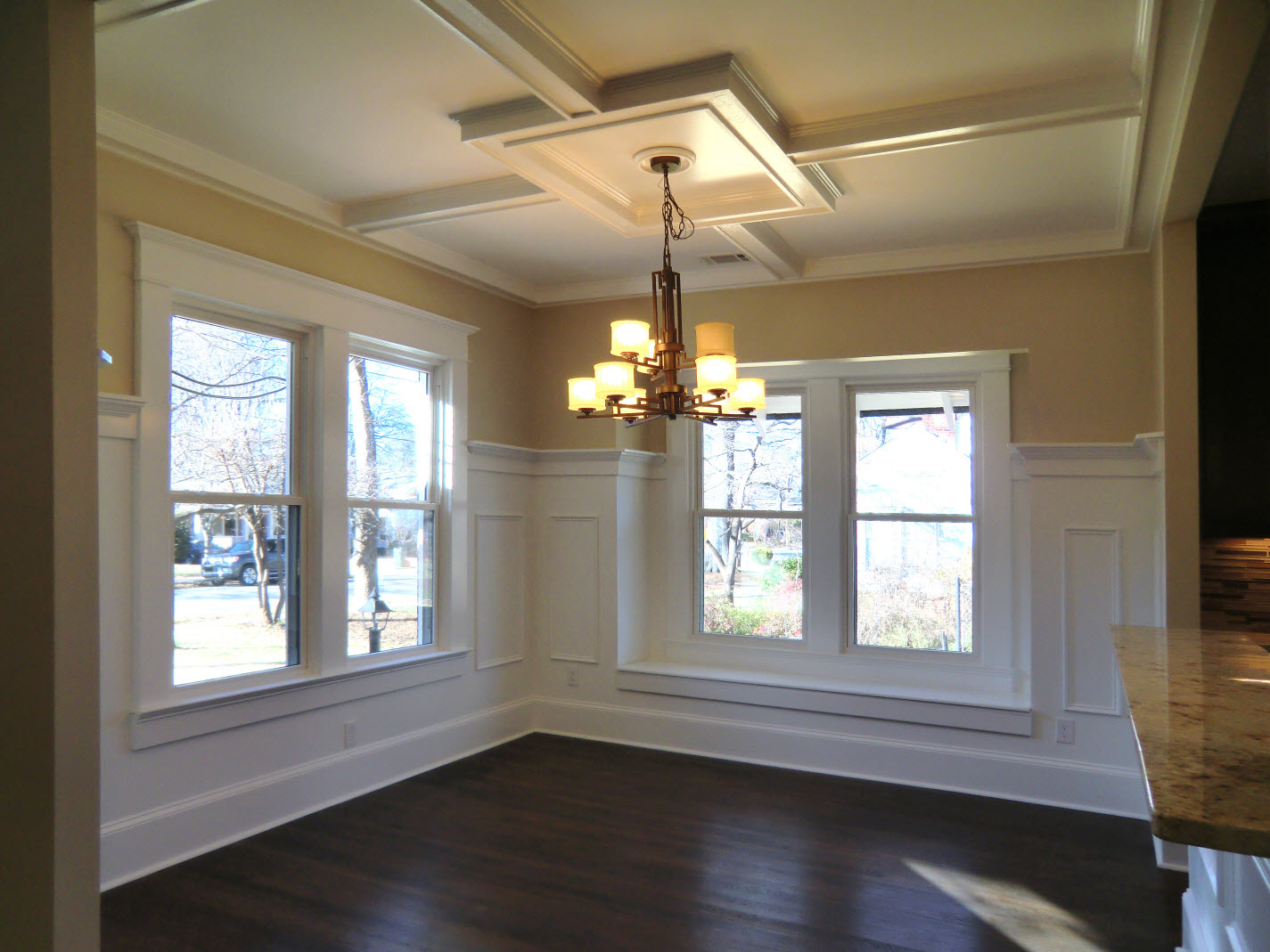 Dining Room with coffered ceiling with chandelier and window plus wooden floor