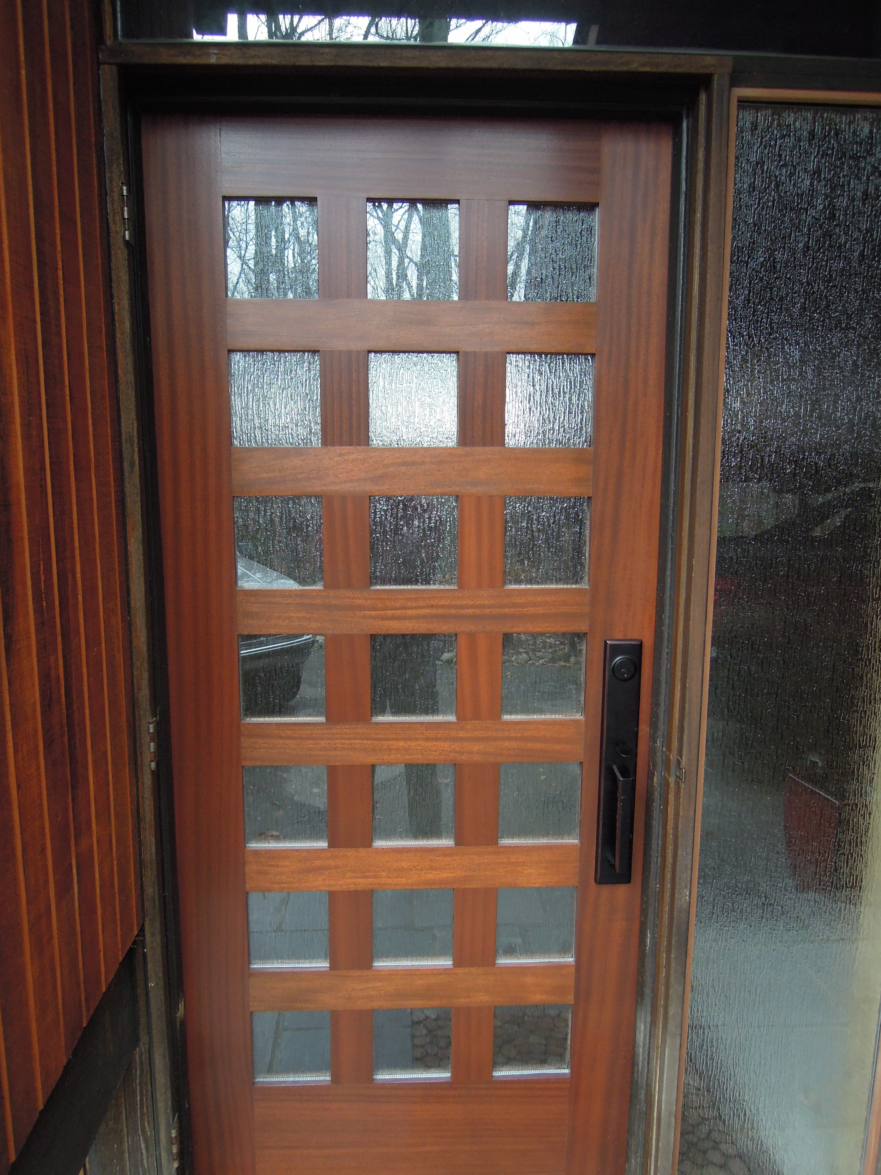 entry door with sidelights with black handle matched with glass wall