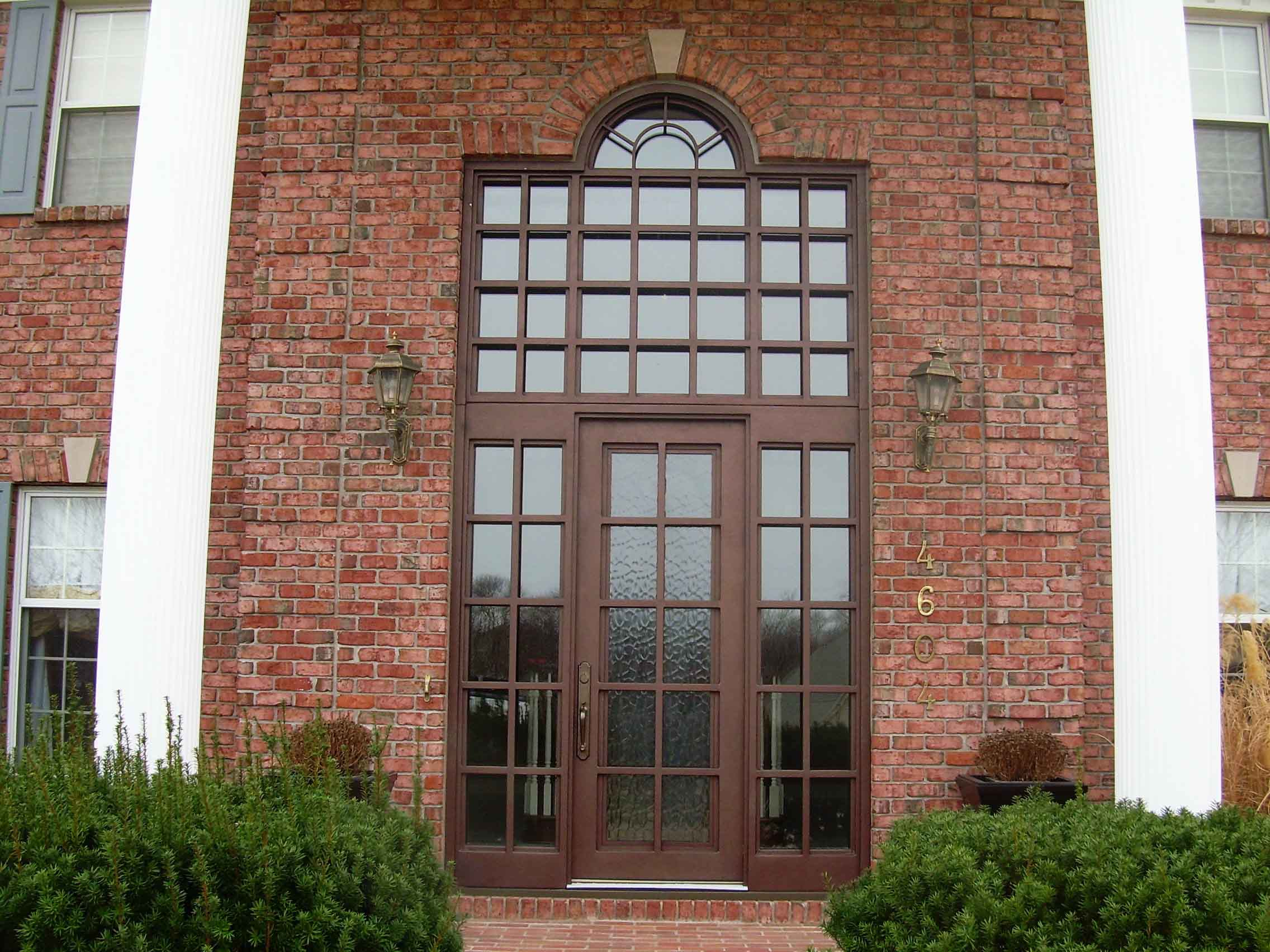 entry door with sidelights with brick wall and double lamp