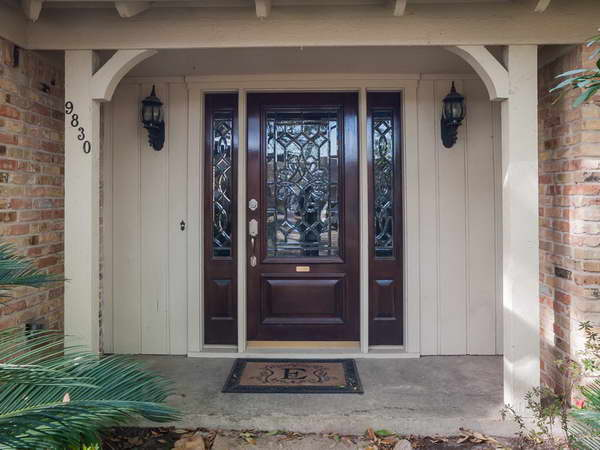 entry door with sidelights with double lamps on wall and ceramics floor plus doormat