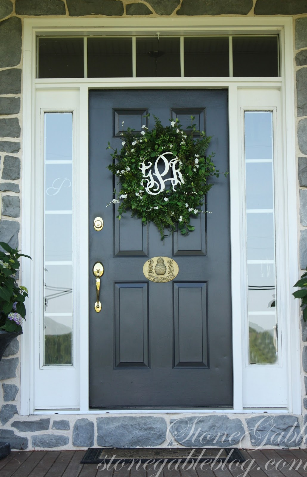 entry door with sidelights with golden handle matched with stone wall and bouquet