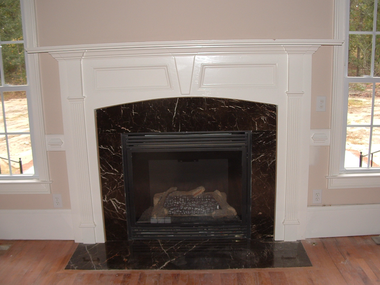 fireplace mantel kits between two windows on wheat wall plus wooden floor