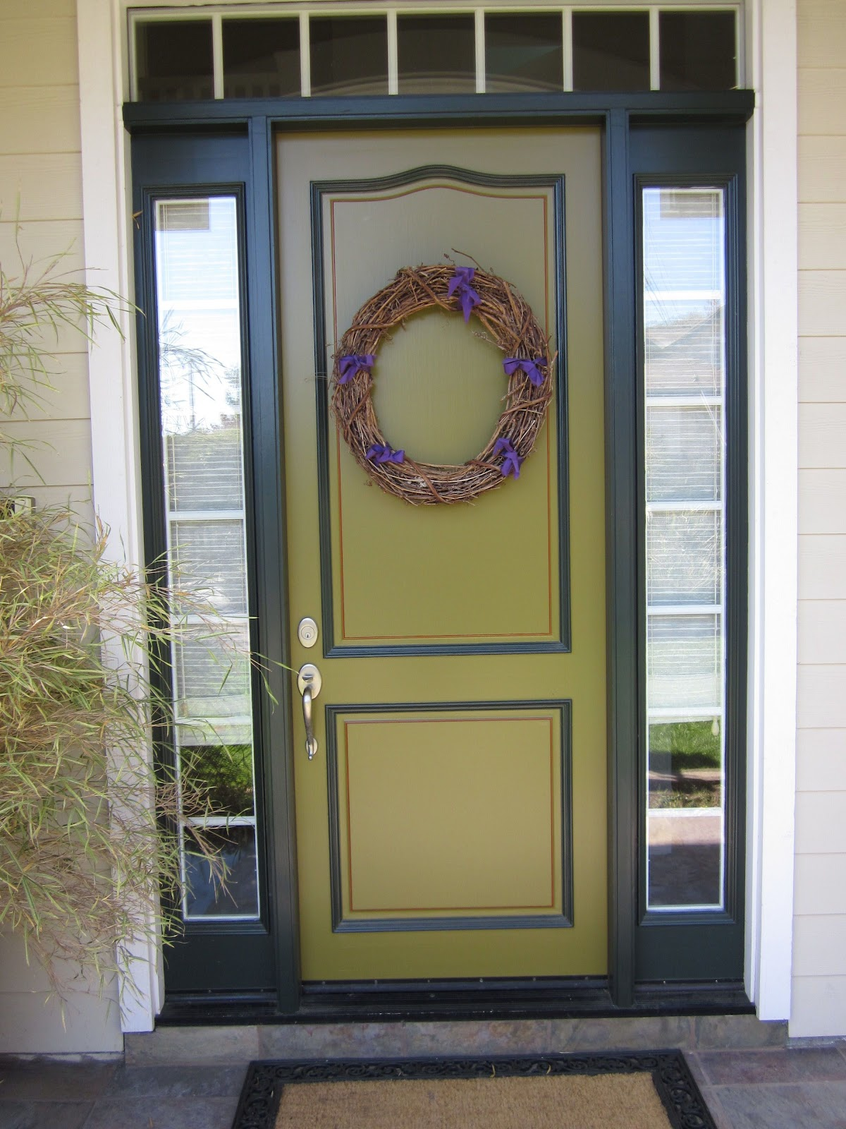 green entry door with sidelights with wheat wall and glass window
