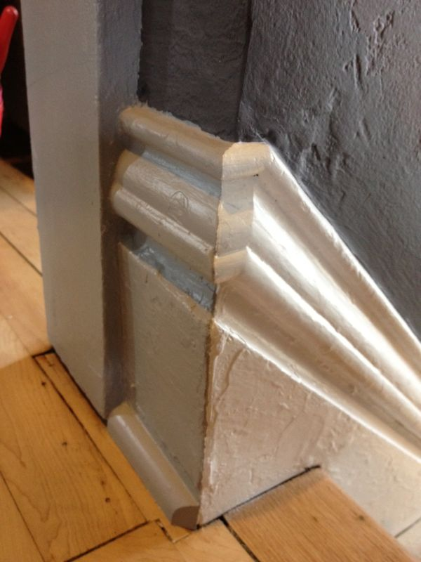grey baseboard molding for wooden stairs area