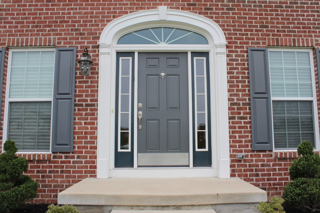 grey entry door with sidelights with brick wall and double window