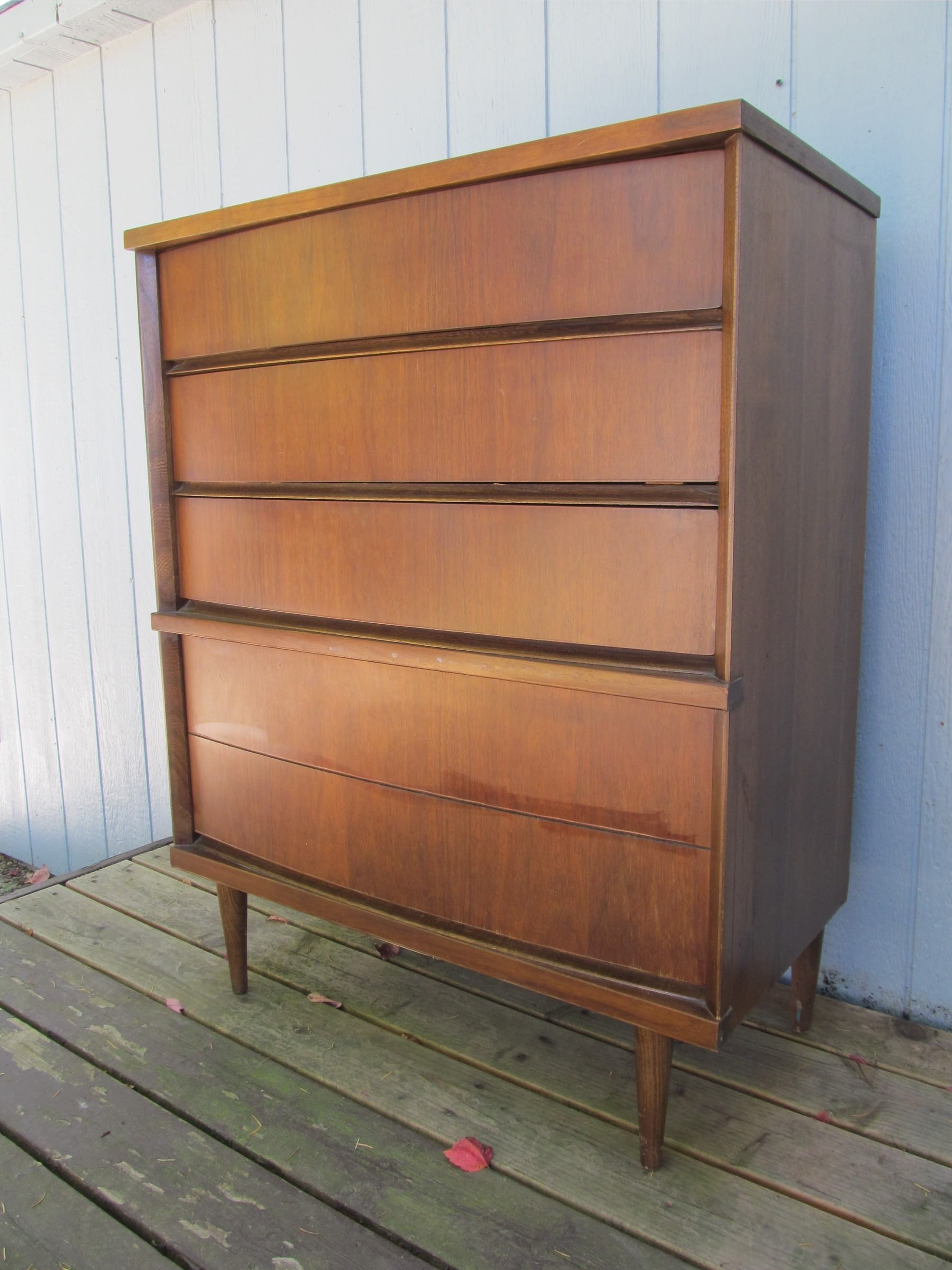 high mid century dresser on wood floor before white wall