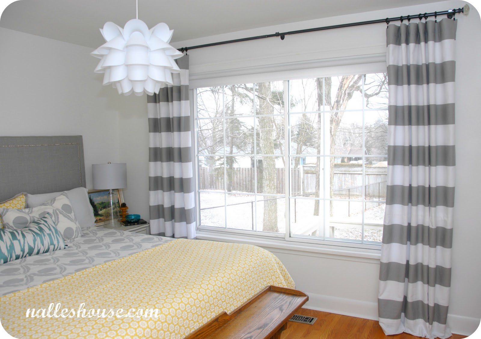 horizontal striped curtains with king sized bed and wooden floor