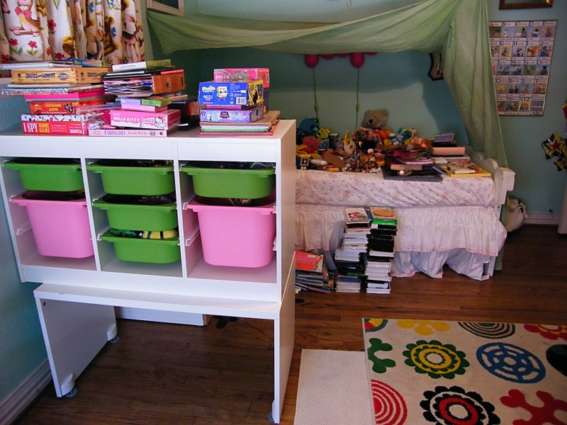 Ikea toy storage filled with green and pink boxes with bedding full of toys with wooden floor and floral carpet