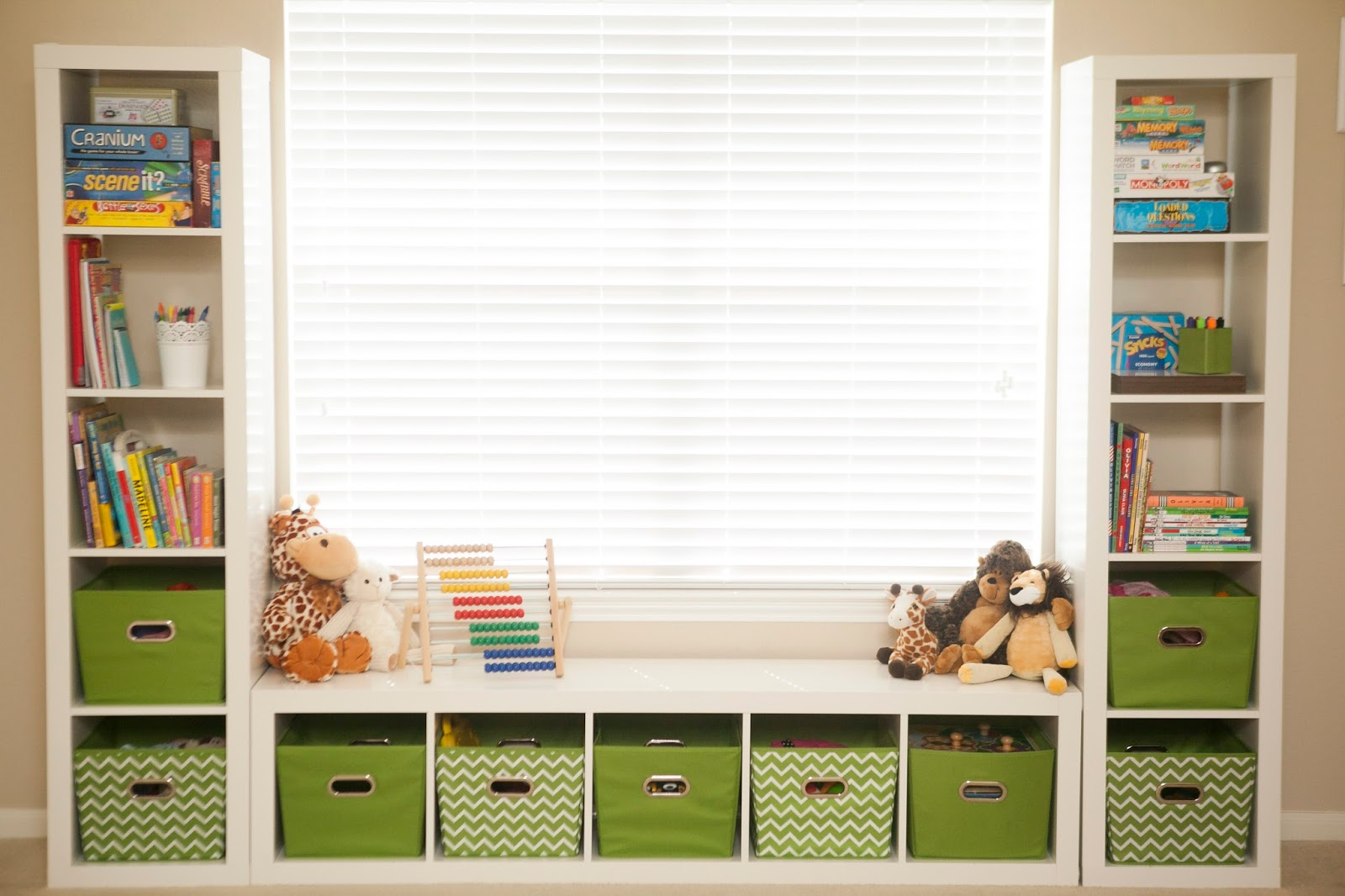 ikea toy storage in white and green nuance with dolls above with window