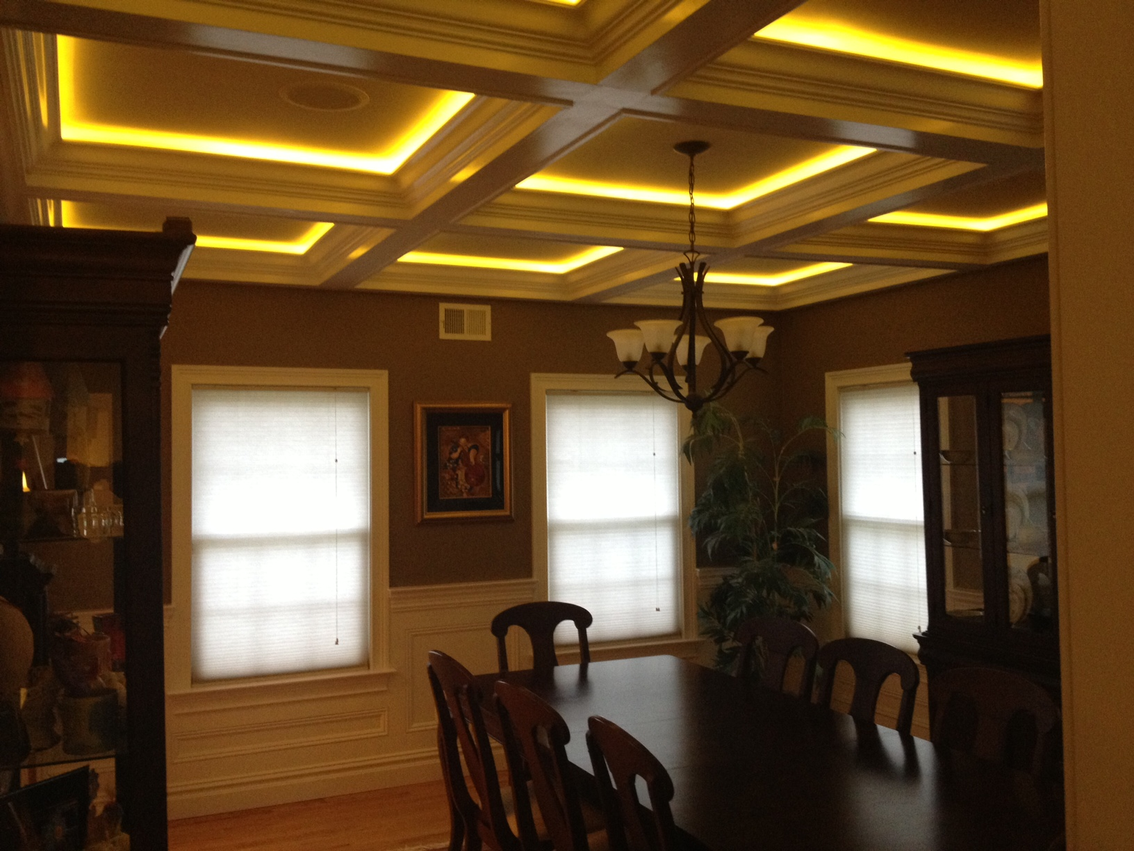 lightening coffered ceiling with chandelier and wooden dining table plus window for beautiful dining room
