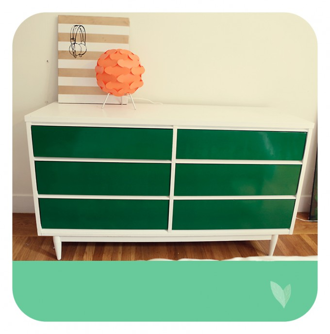 Mid Century Dresser In Grren And White With Paper Bag Above And Wooden Floor