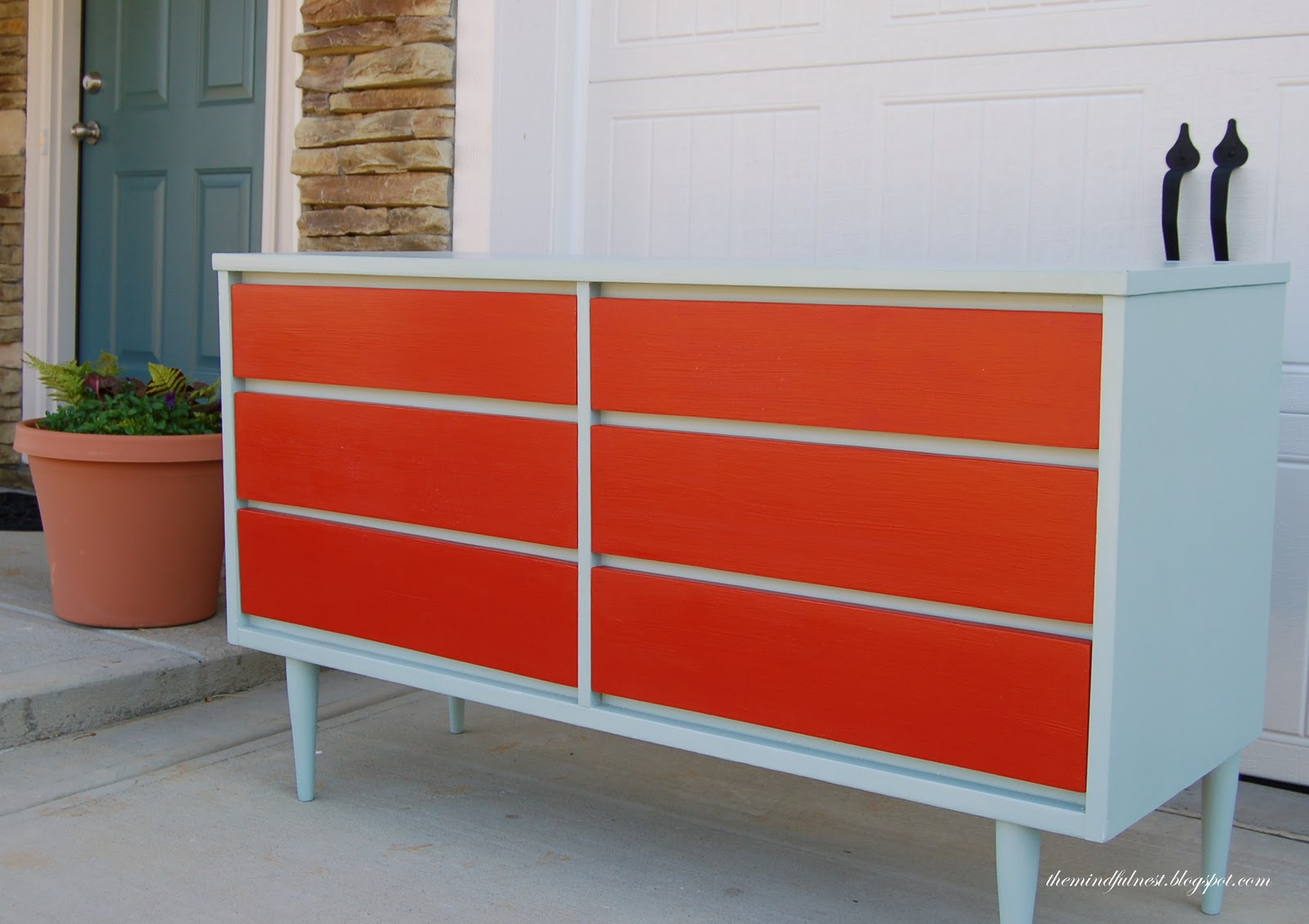 Mid Century Dresser in orange and white with white legs before white wall