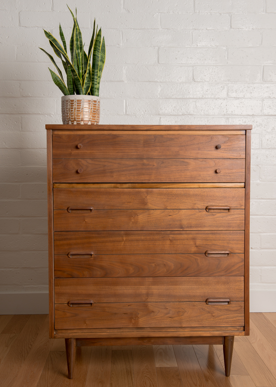 Mid Century Dresser with flower vase above with brick wall and wooden floor