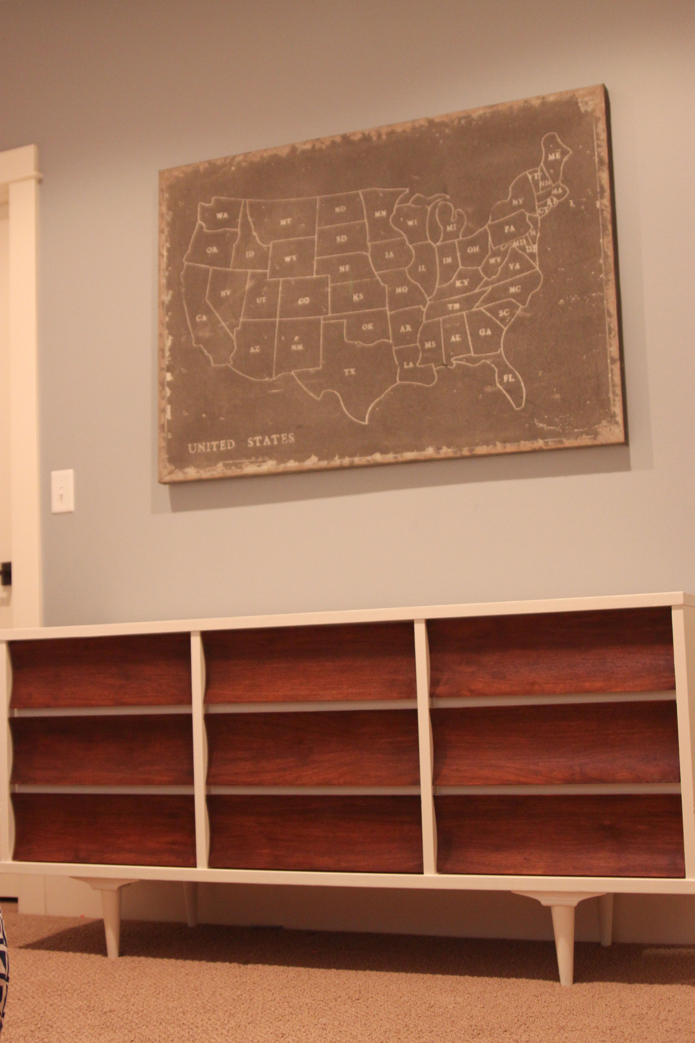 mid century dresser with united state sketch on grey wall