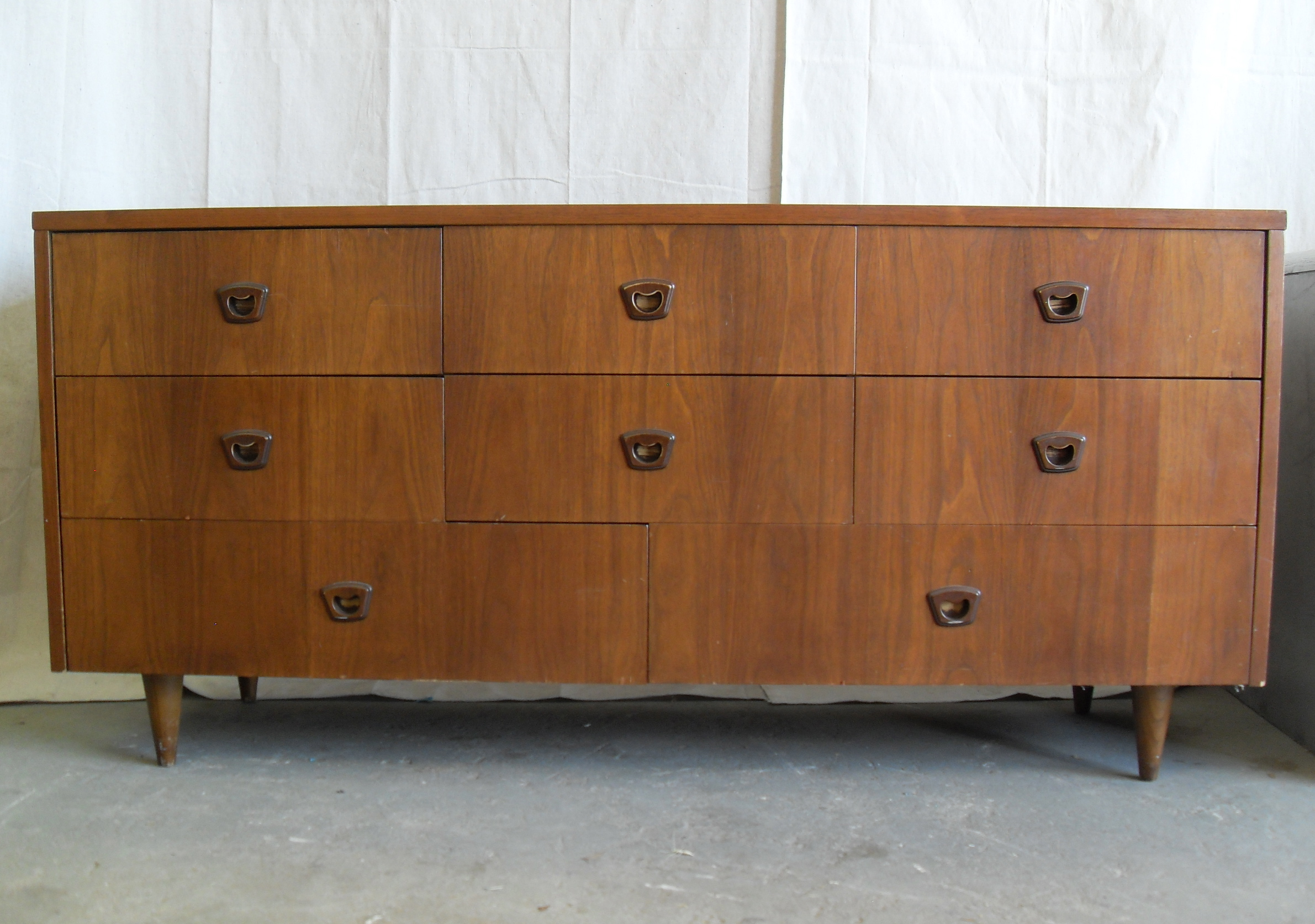Mid Century dresser with white wall and grey floor