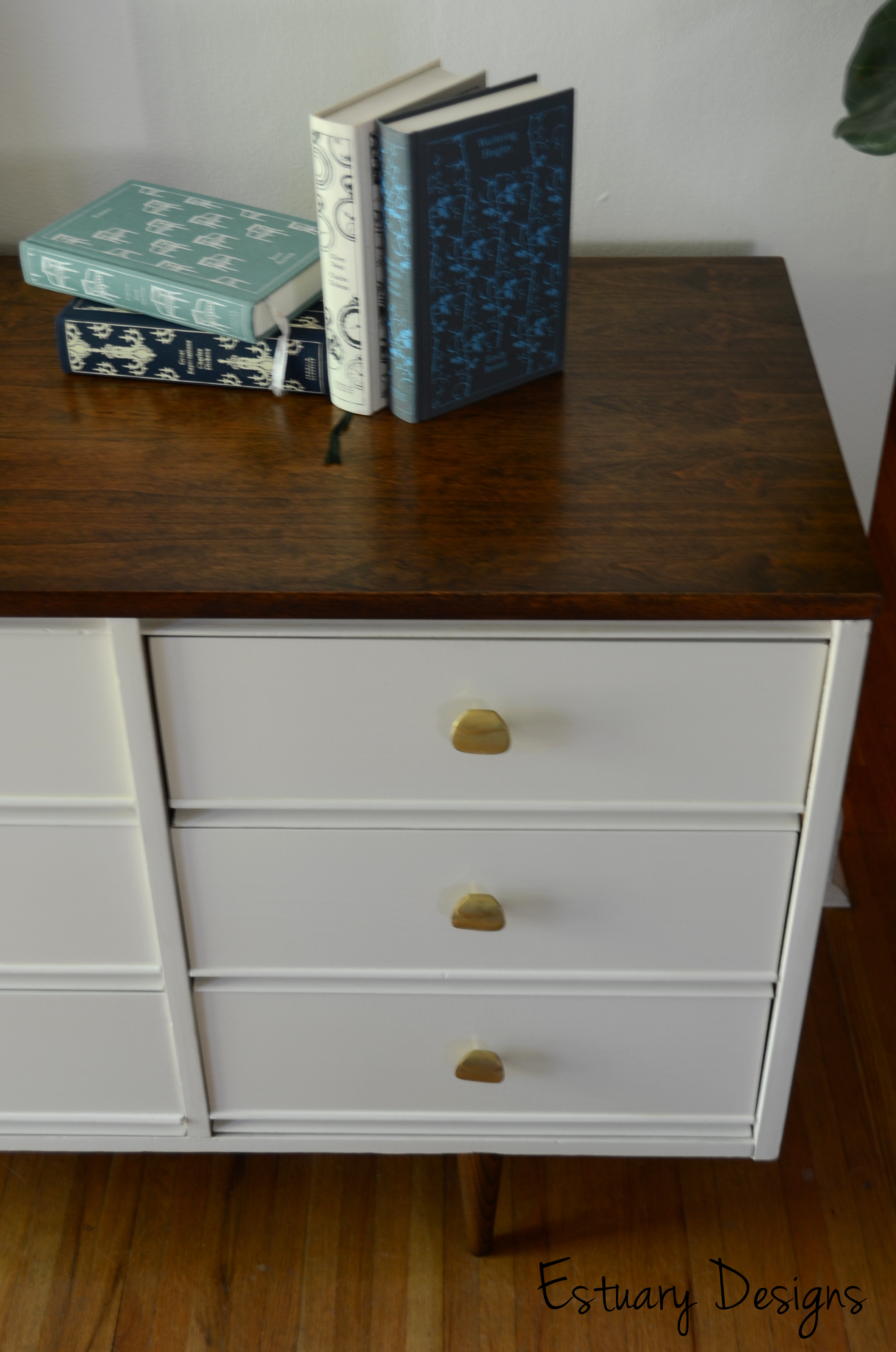 Mid Century Dresser with yellow handle plus books above before white wall