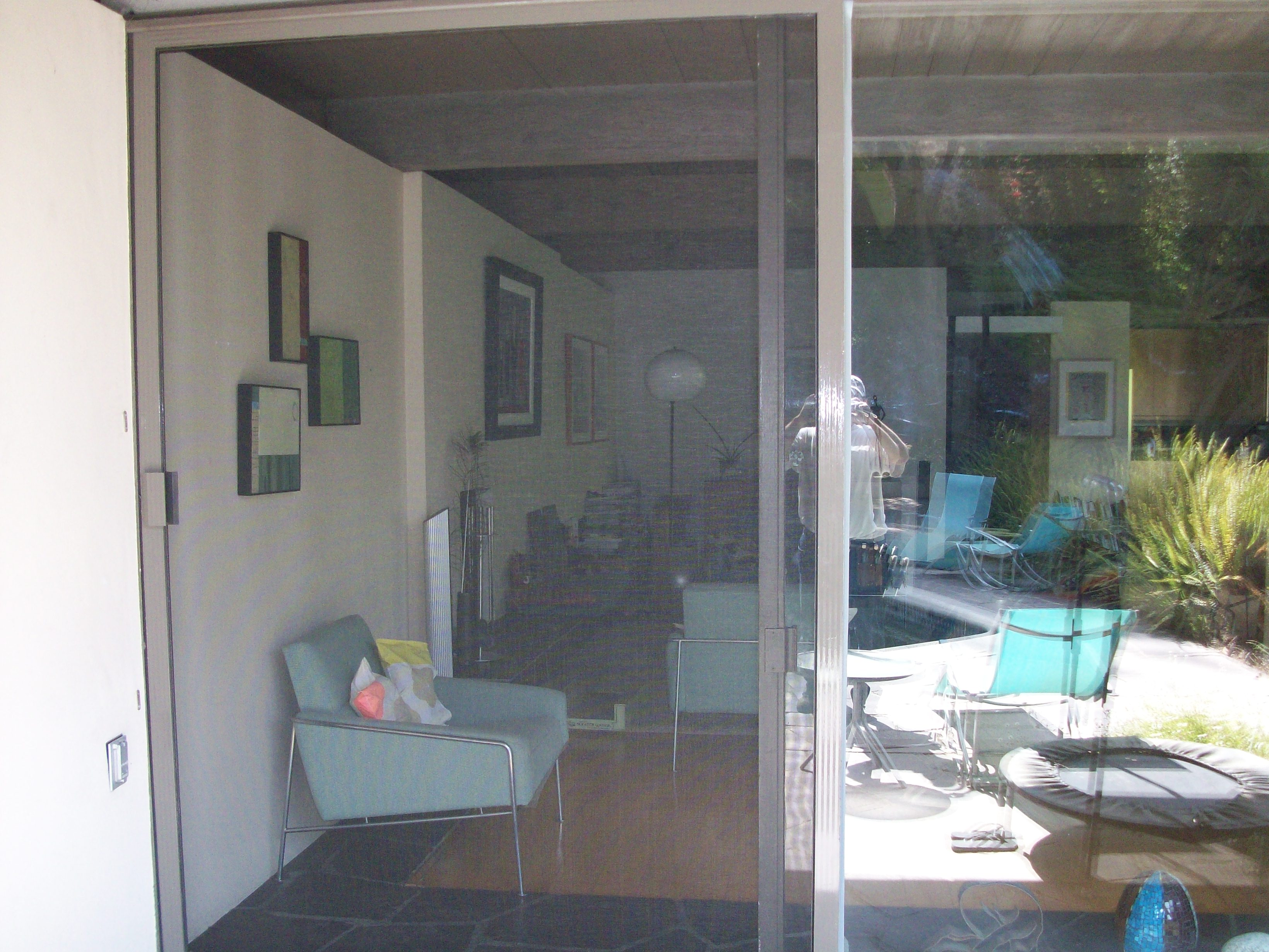 modern Retractable screen doors with chair and black ceramics floor