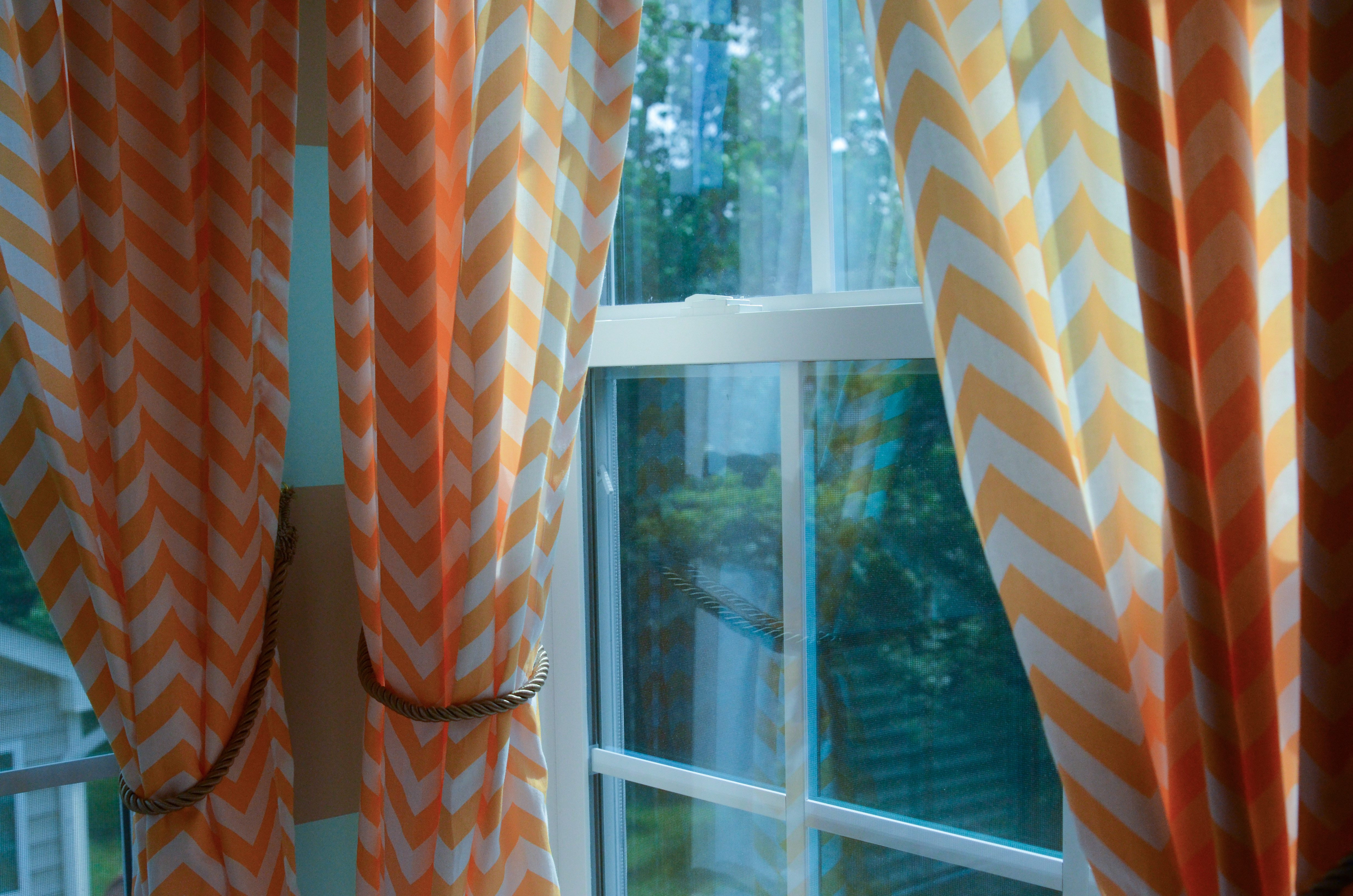 orange and white Chevron Curtains on window and horizontal striped white and orange wall