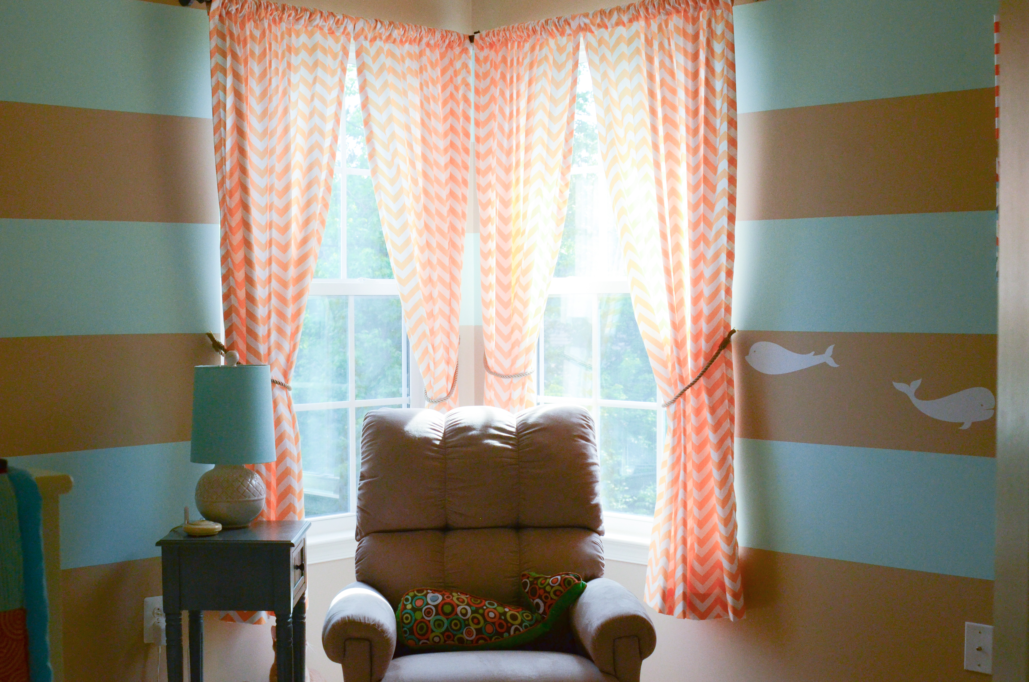 pretty pink chevron curtains with horizontal brown and blue striped wall plus brown sofa and floral cushions
