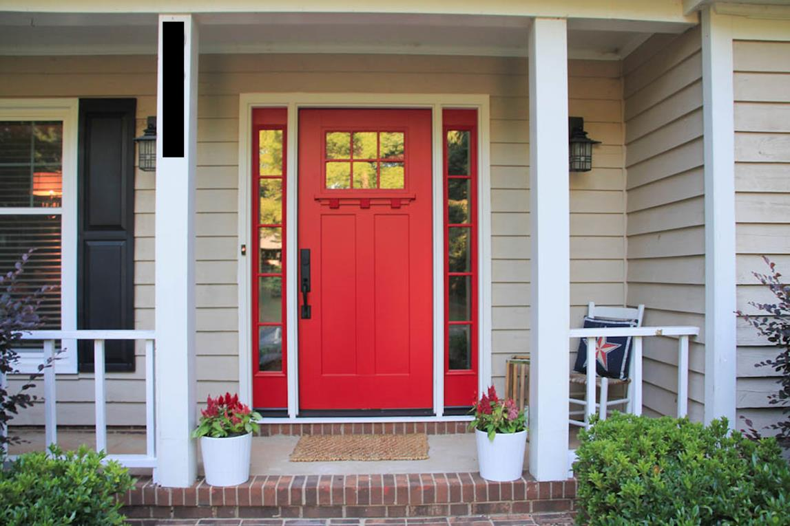 red entry door with sidelights with white sills and double lamp on wall