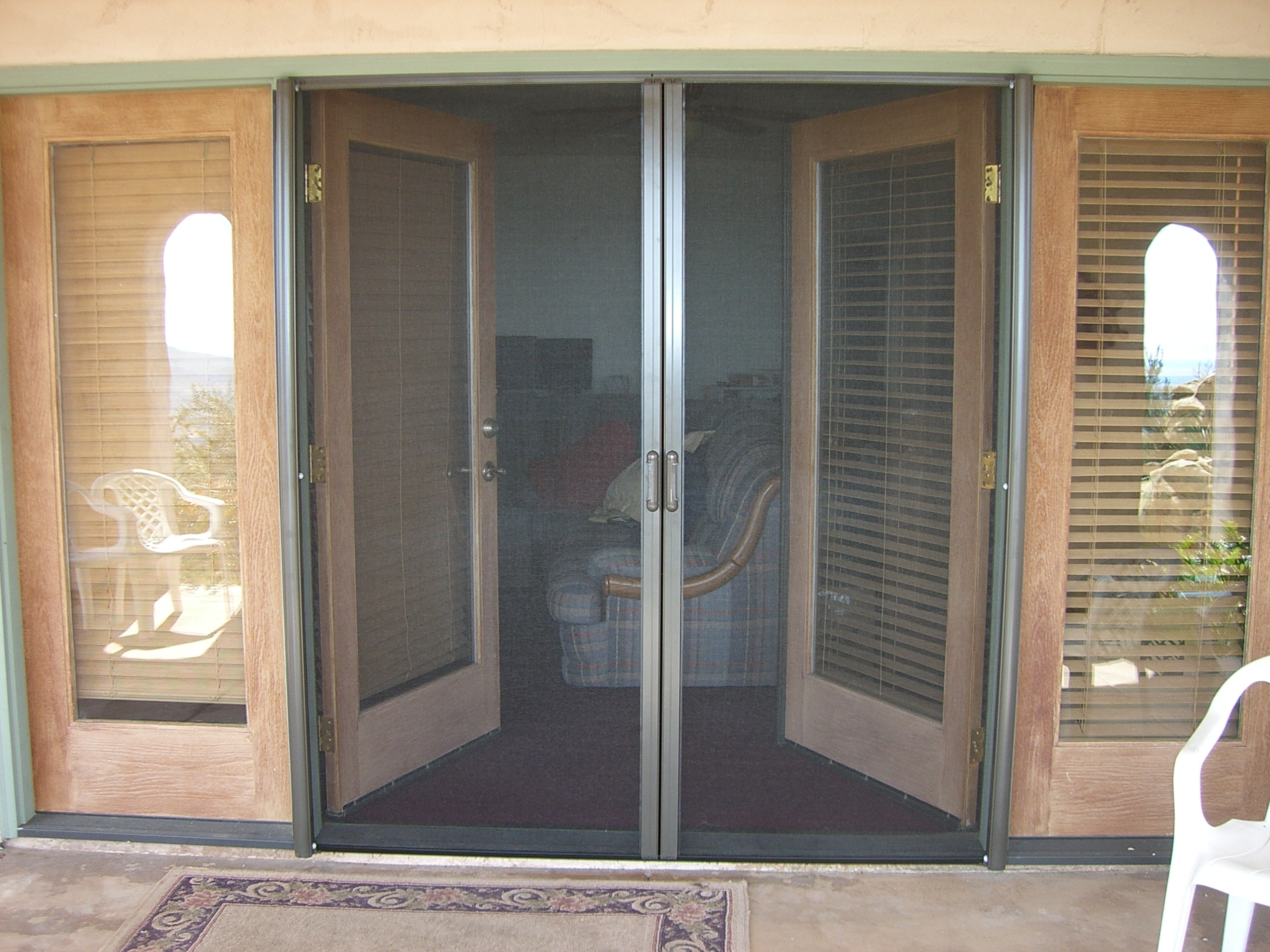 Retractable Screen doors between wondows plus chairs and ceramics floor