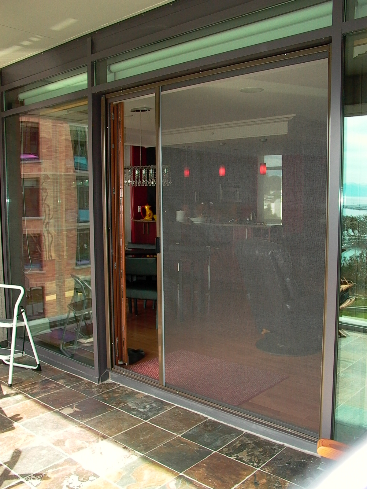 Retractable screen doors in grey with chair and cramics floor for terrace