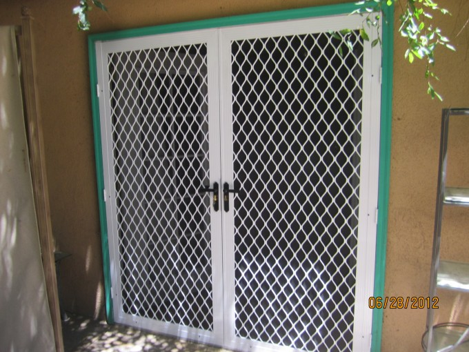 Retractable Screen Doors In White And Green Theme With White Handle Matched With Yellow Wall