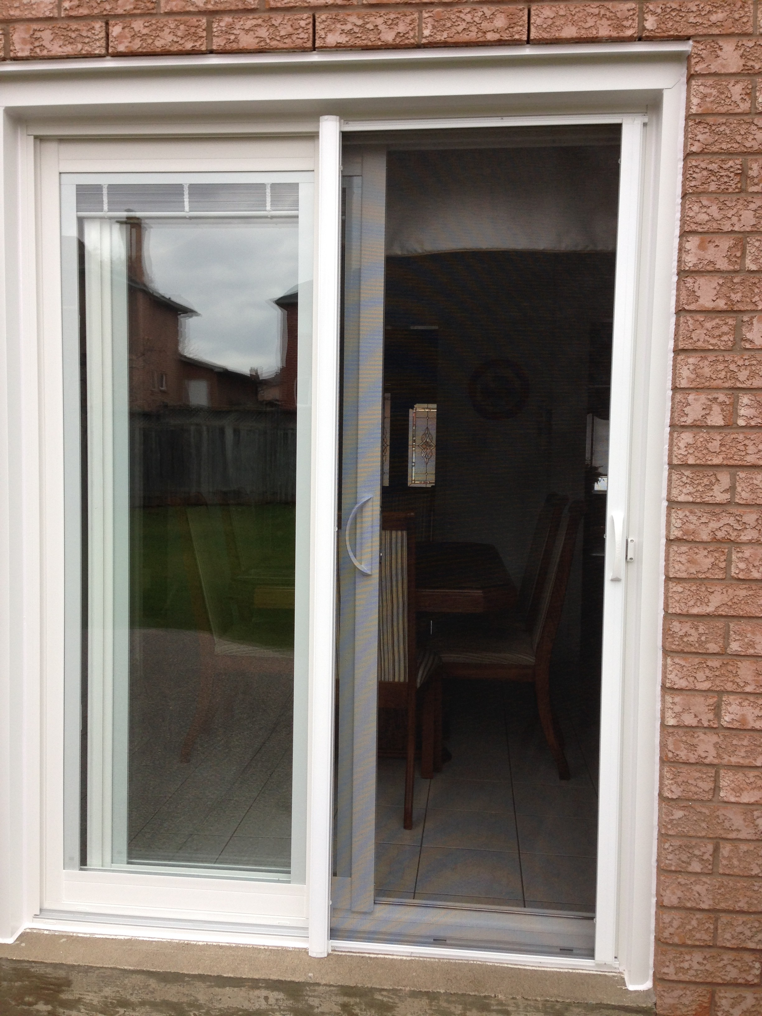Retractable Screen Doors in white matched with brick wall