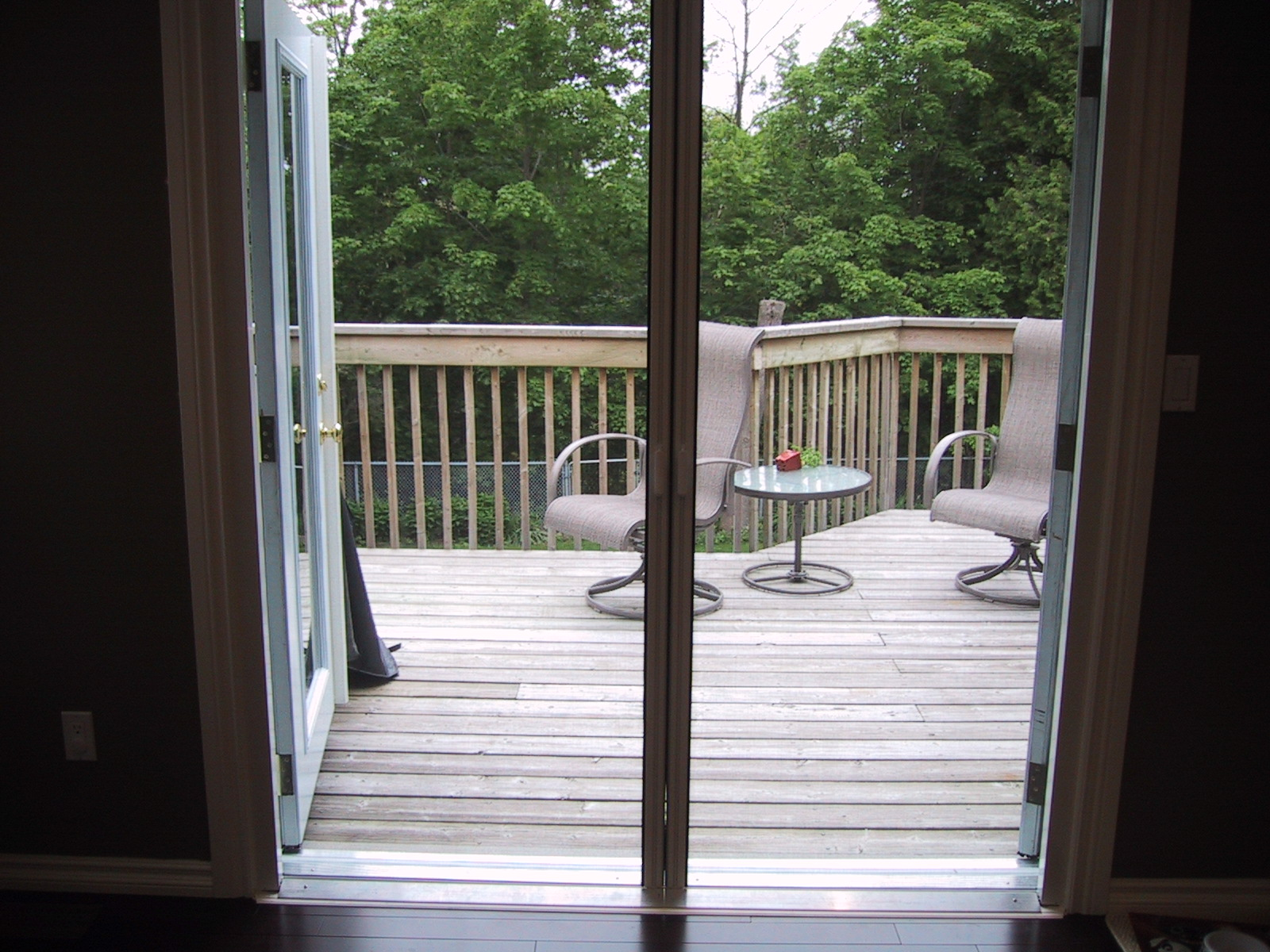 Retractable Screen doors matched with wooden floor before balcony