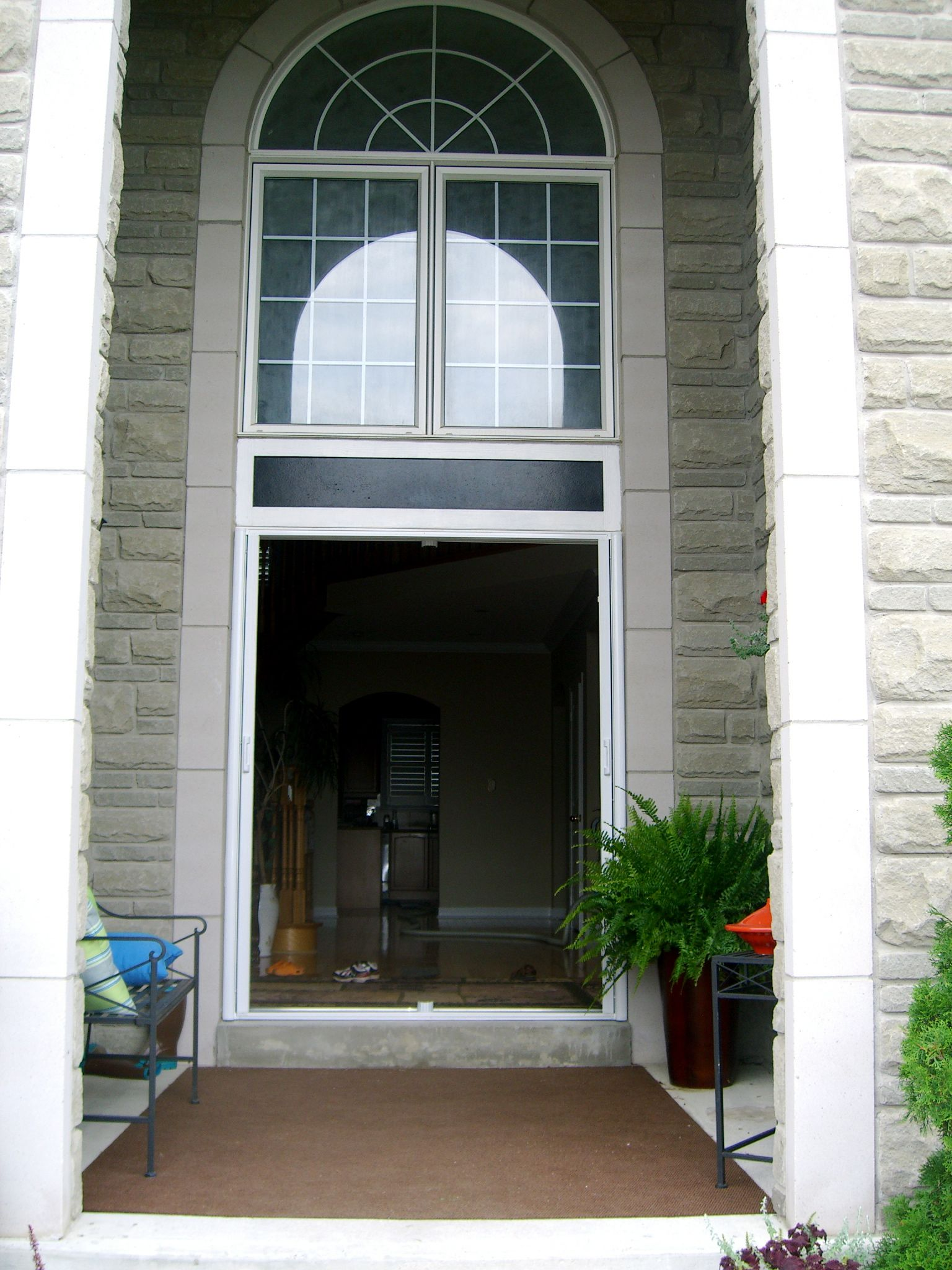Retractable screen doors with arch above matched with wooden floor before beautiful balcony