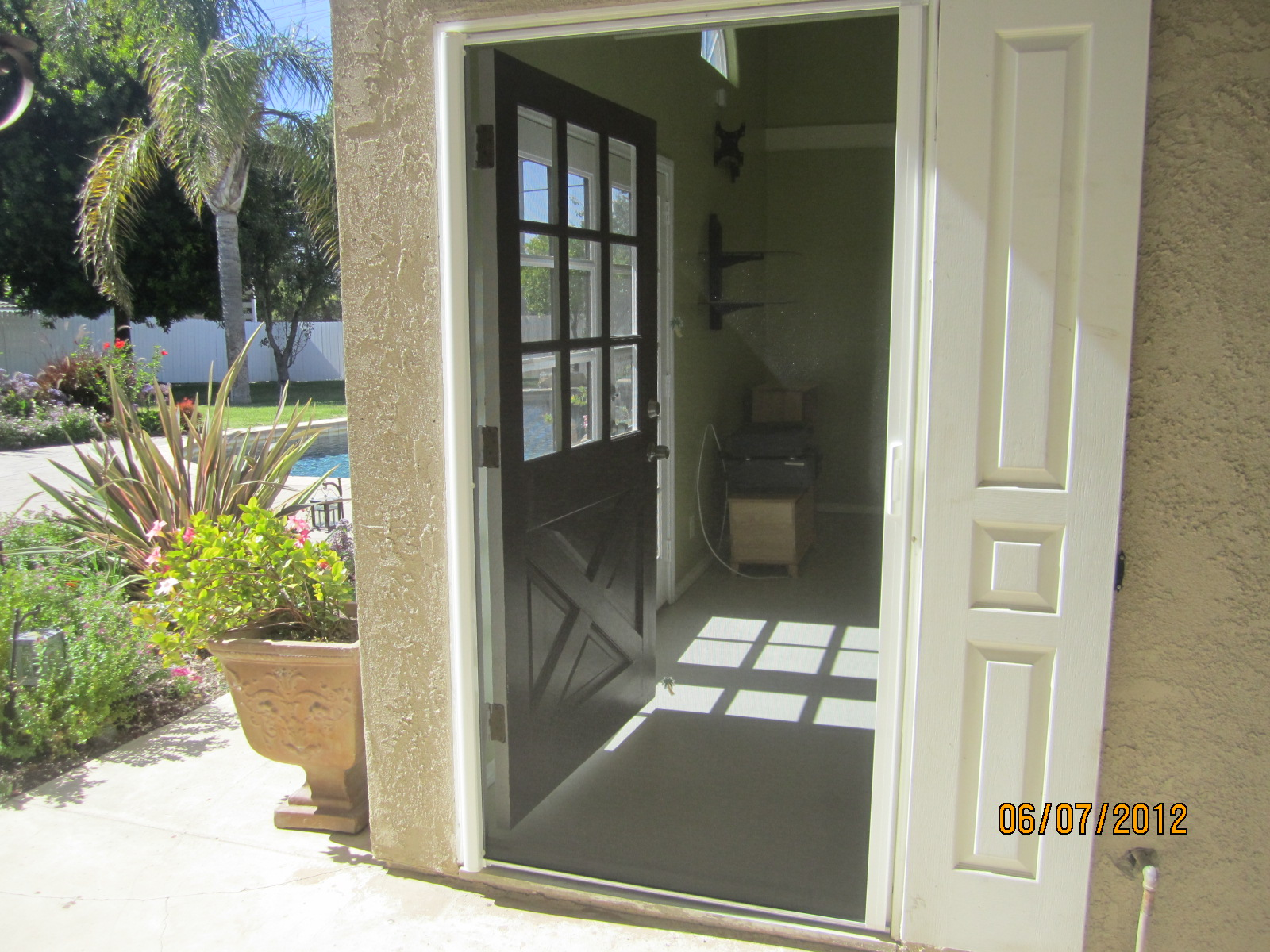 Retractable Screen Doors with black color and cream wall