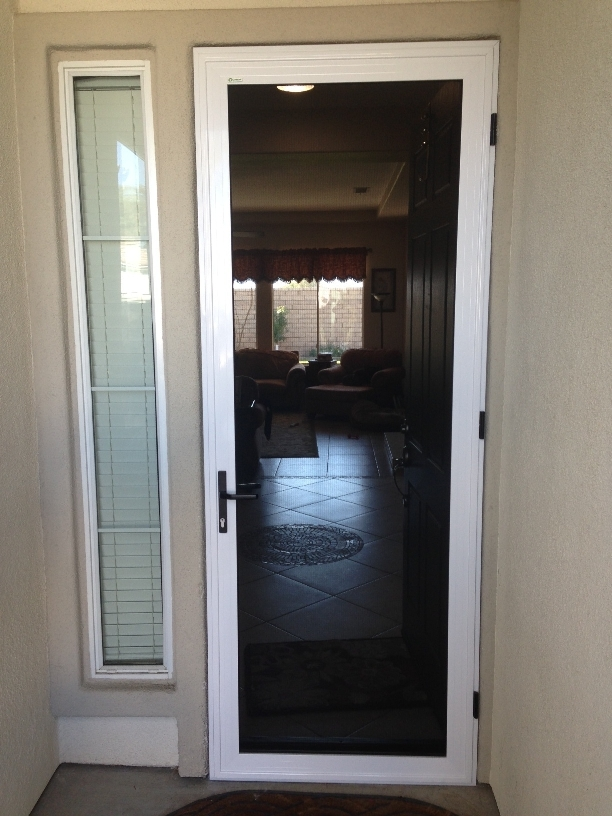 Retractable screen doors with black handle and cream wall