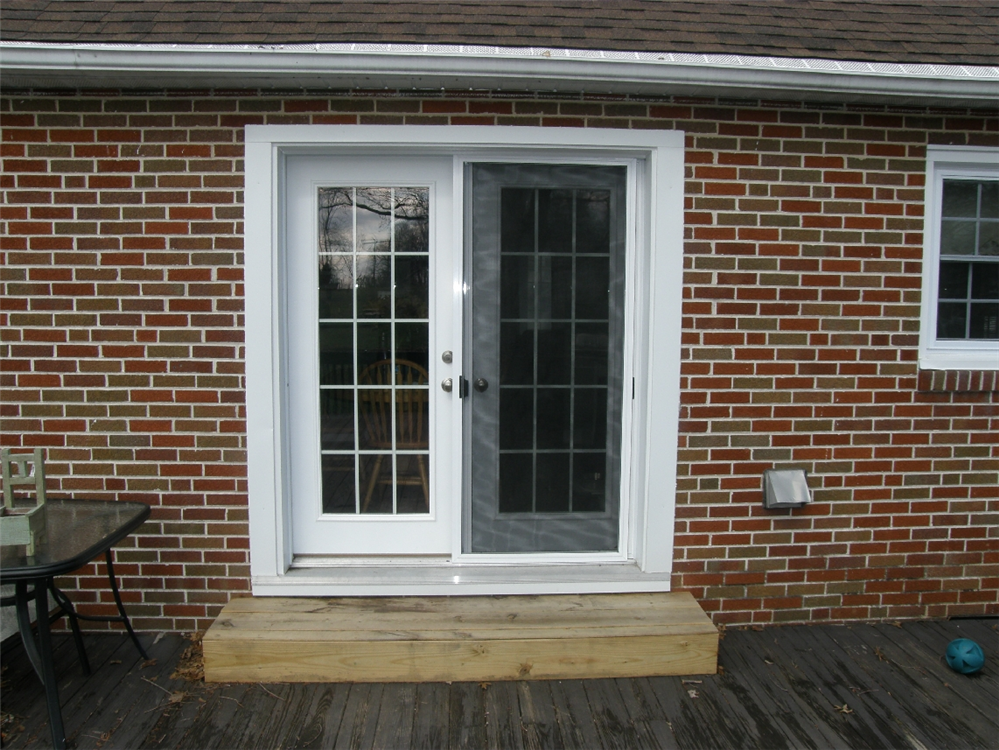 Retractable Screen Doors with brick wall and white window plus wood floor