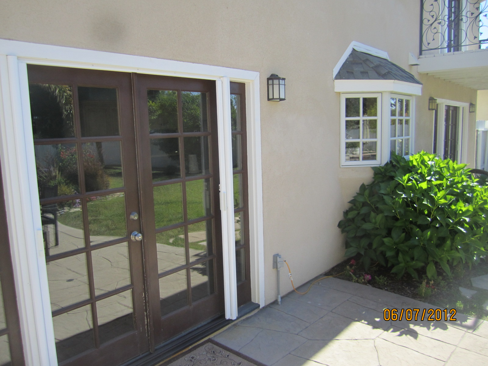 Retractable screen doors with doorknob handle and white baseboard molding