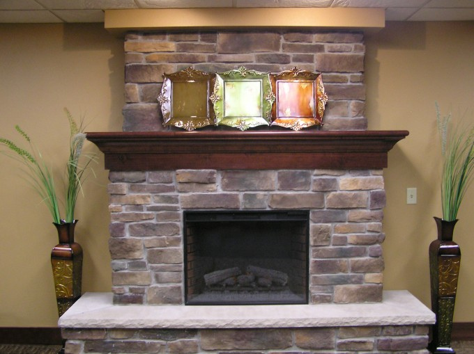 Stone Toucheing Of Fireplace Mantel Kits With Frame Space Above And Tan Wall