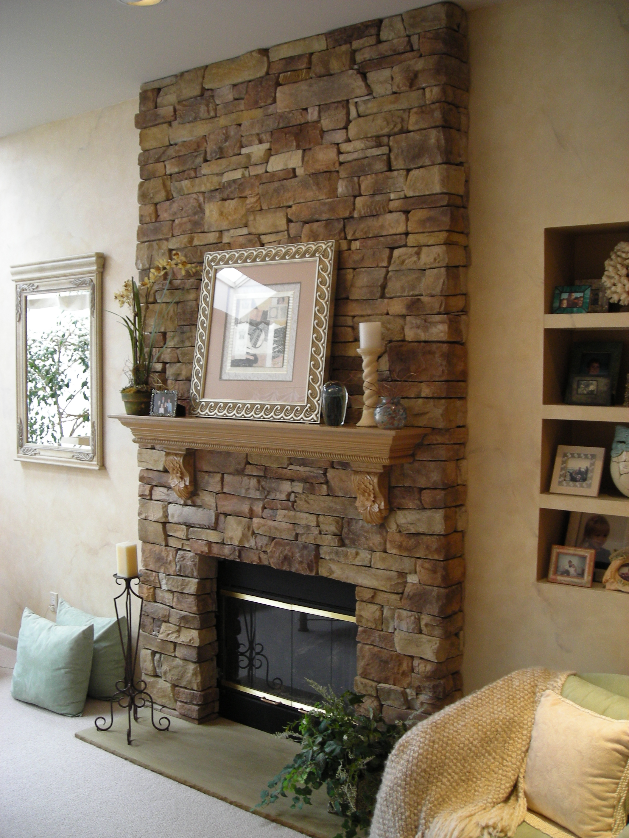 Stone Veneer panels Fireplace with pictures and mirror on wall for family room ideas