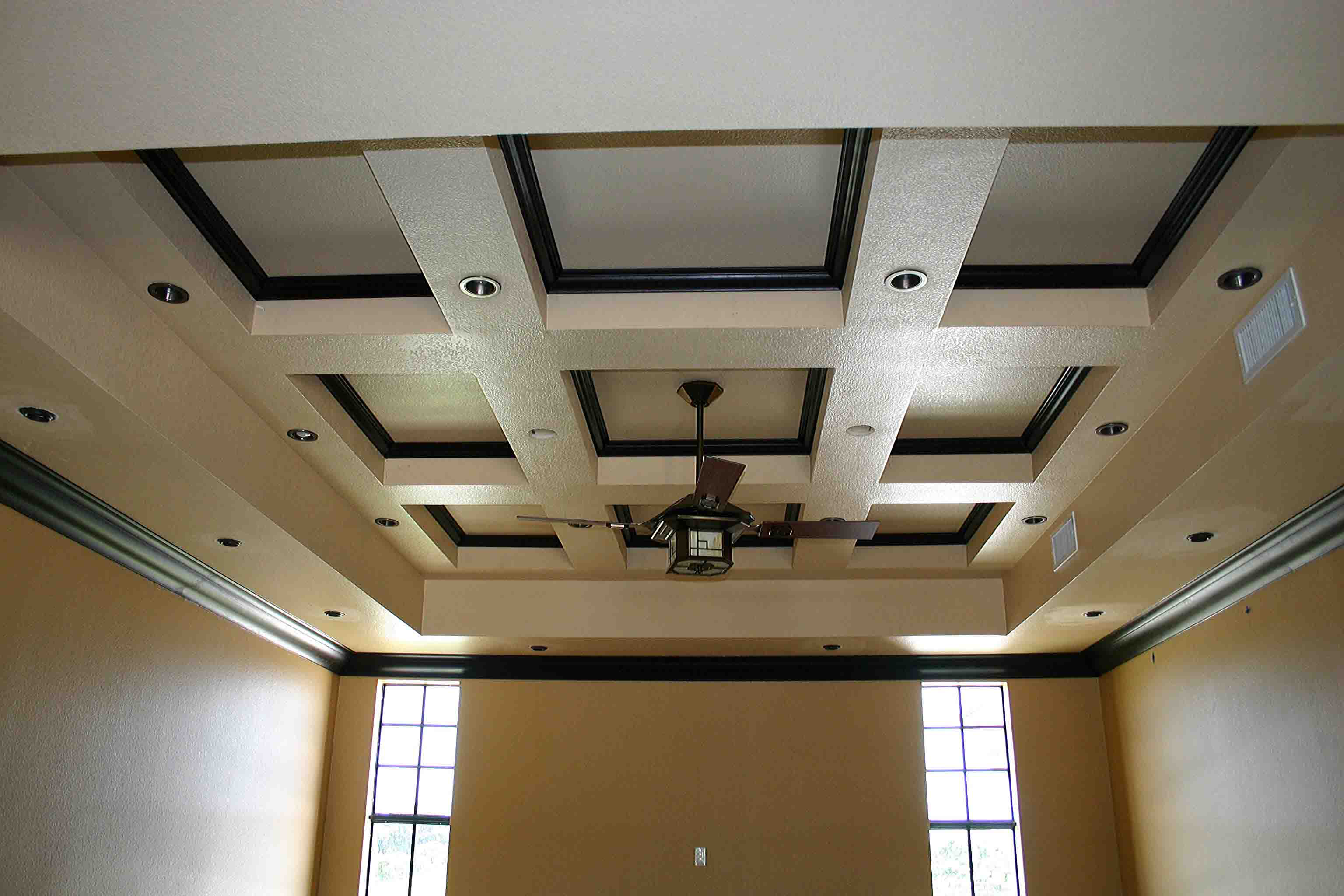 stunning Coffered Ceiling in white and black theme plus lights and chandelier matched with cream wall plus two single hung windows