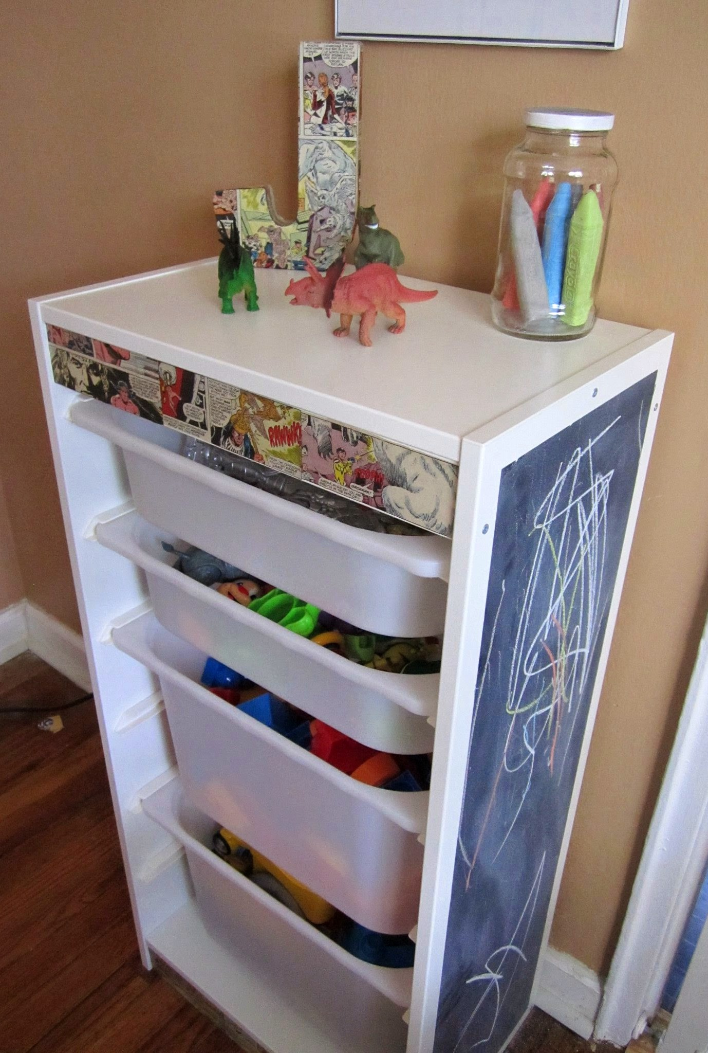 tall ikea toy storage fillled with toys and mini blackboard beside with cream wall
