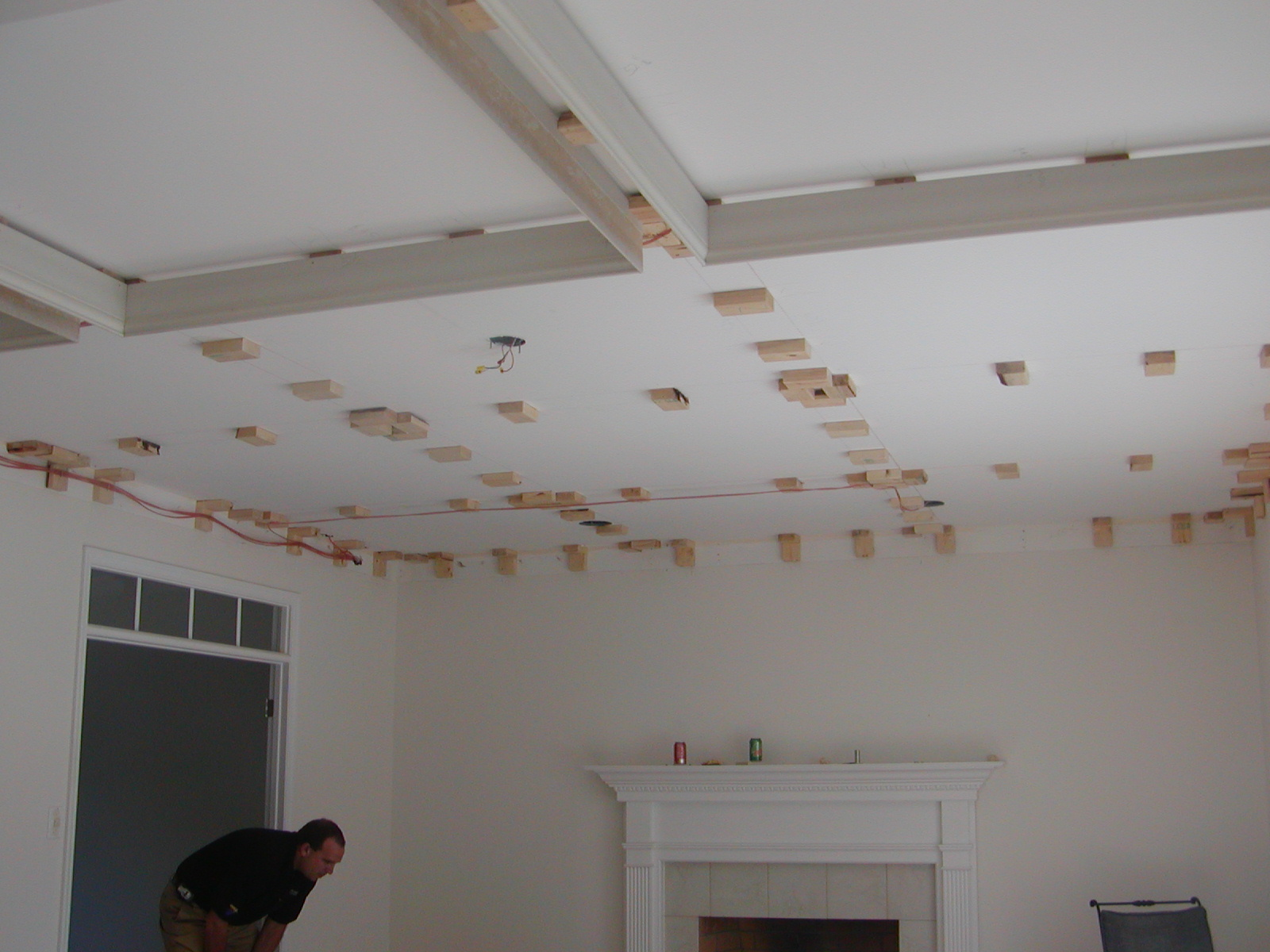 Toronto patterned coffered ceiling installation on white room with fireplace